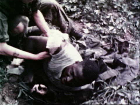 1960s ha medic bandaging a wounded soldier in the field / vietnam - marines stock videos & royalty-free footage