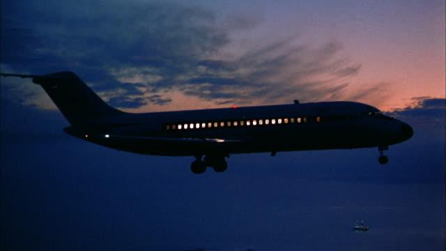 1960s medium shot 707 jet plane flying at night w/lights in windows - aeroplane stock videos & royalty-free footage