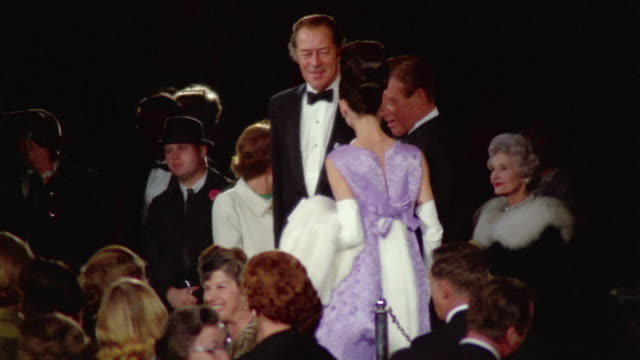 "1960s medium shot audrey hepburn twirling and showing off dress with rex harrison at ""my fair lady"" premiere - festlich gekleidet stock-videos und b-roll-filmmaterial"