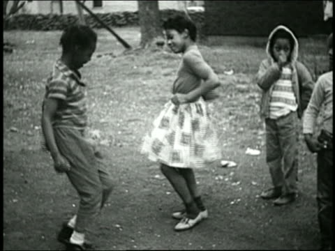 1960s medium shot black boy and girl dancing outdoors / others in background - african american ethnicity stock videos & royalty-free footage
