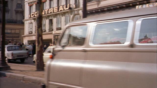 vidéos et rushes de 1960s medium shot car point of view streets of paris w/pedestrians and stores - 1960