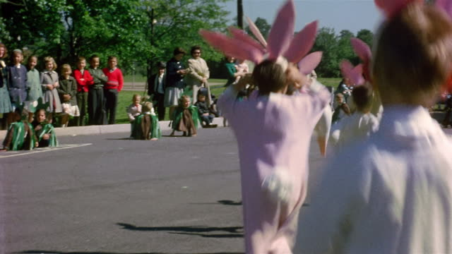 1960s medium shot children dressed up in bunny costumes hopping down street in parade / people watching in background