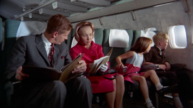 1960s medium shot family w/two children sitting on airplane and reading flight brochures