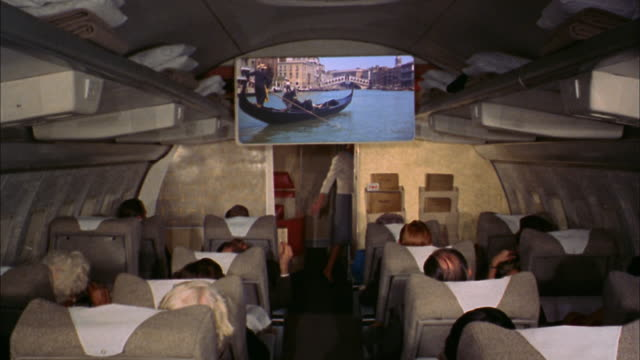 1960s medium shot first class passengers watching film on screen in airplane / flight attendant working