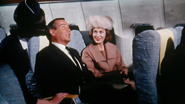 1960s medium shot flight attendant speaking to couple on passenger airplane