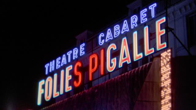 vidéos et rushes de 1960s medium shot  'folies pigalle' neon sign at night / tilt down marquee and people outside club / paris - signalisation