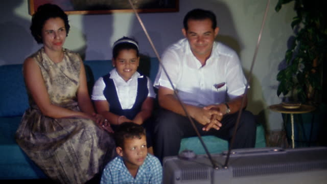 1960s medium shot Hispanic family watching television, laughing and pointing in living room