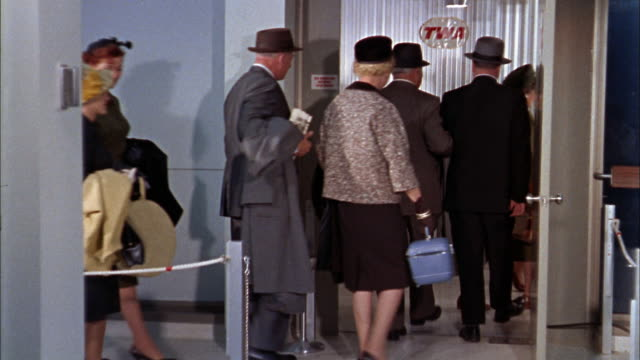 1960s medium shot line of passengers walking through twa jetway entrance to board airplane - twa video stock e b–roll