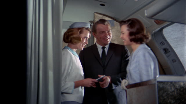 1960s medium shot male and female flight attendants taking tickets / greeting woman + children boarding plane