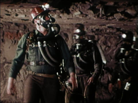 1960s medium shot miners wearing gas masks and headlamps walking toward cam inside cave - rescue stock videos & royalty-free footage