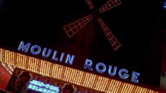 vidéos et rushes de 1960s medium shot neon moulin rouge nightclub sign w/windmill at night / paris - signalisation