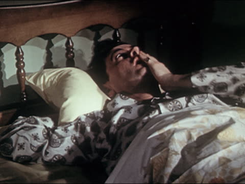 vidéos et rushes de audio 1960s medium shot pan man and woman (married couple) lying awake in separate beds - frustration
