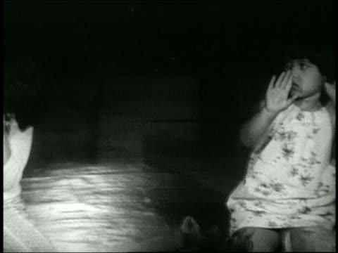 1960s medium shot pan row of small girls learning hula dancing - endast flickor bildbanksvideor och videomaterial från bakom kulisserna