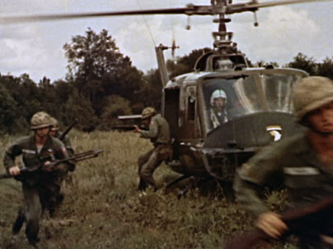 1960s medium shot pan us soldiers climb out of helicopter holding guns / running across field / vietnam - vietnamkrieg stock-videos und b-roll-filmmaterial