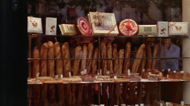 stockvideo's en b-roll-footage met 1960s medium shot pan woman buying baguettes at boulangerie and exiting / paris, france - franse cultuur