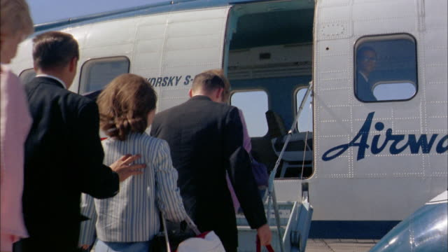 1960s medium shot passengers climbing steps and boarding sikorsky s-61 helicopter / nyc - military helicopter stock videos & royalty-free footage