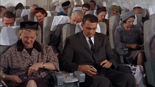 1960s medium shot passengers fastening seat belts on 707 plane / man smoking and talking - crew stock videos & royalty-free footage