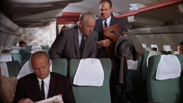 1960s medium shot passengers finding seats on 707 airplane and putting luggage in racks