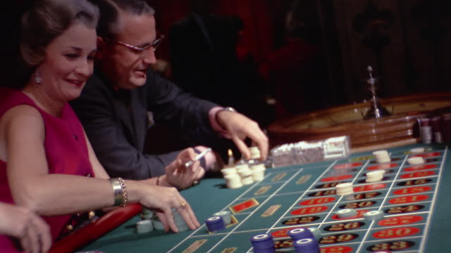 1960s medium shot people placing chips on table at roulette wheel - gambling stock videos and b-roll footage