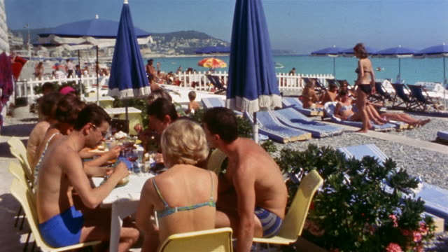 1960s medium shot people sitting at tables and eating + lying on beach chairs / Cannes, France