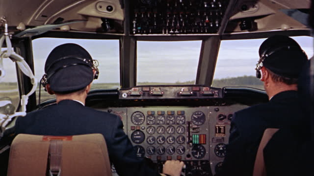 1960s medium shot pilots sitting at the controls in cockpit of airplane and landing