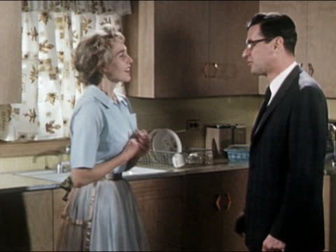 1960s medium shot reenactment housewife in kitchen welcoming husband home from work / hugging - ehemann stock-videos und b-roll-filmmaterial