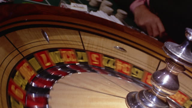 1960s medium shot roulette wheel spinning - casino stock-videos und b-roll-filmmaterial