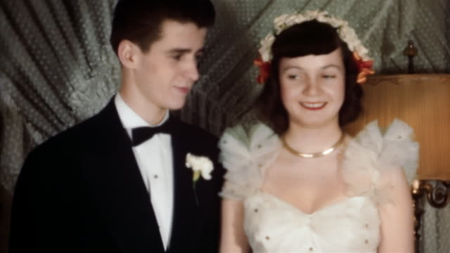 1960s medium shot teenage boy in tuxedo and teenage girl in prom dress smiling at cam - coppia di adolescenti video stock e b–roll
