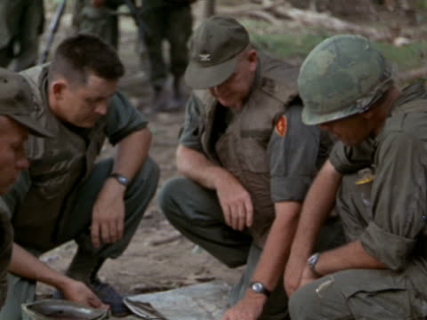 1960s medium shot three US servicemen crouching down to read map on the ground / Vietnam