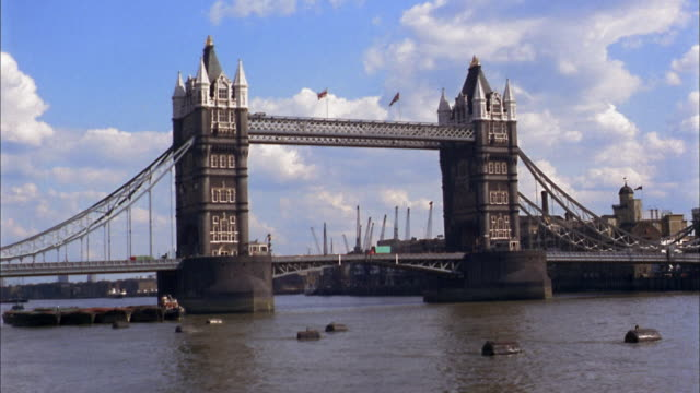 vidéos et rushes de 1960s medium shot tower bridge w/traffic and thames river - 1960