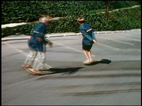 1960s medium shot tracking shot 2 boys in matching jackets skateboarding barefoot in parking lot / california - 1960 stock videos and b-roll footage
