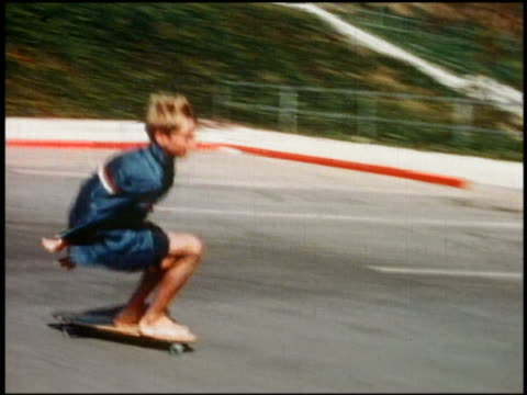 1960s medium shot tracking shot boy skateboarding barefoot in parking lot / california - londonalight stock videos and b-roll footage