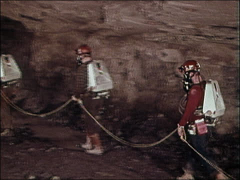 1960s medium shot tracking shot line of miners in gas masks holding rope and walking into cave tunnel / audio - rescue stock videos & royalty-free footage