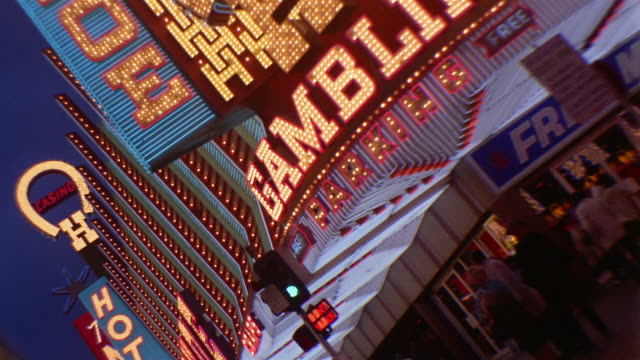 1960s medium shot tracking shot side car point of view neon signs on marquees outside casinos at dusk - casino stock-videos und b-roll-filmmaterial