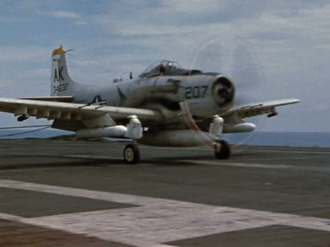 1960s medium shot US Navy airplane landing on aircraft carrier / crew checking it out / wings folding up