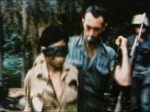 1960s medium shot US soldier escorting blindfolded Viet Cong POW / Vietnam