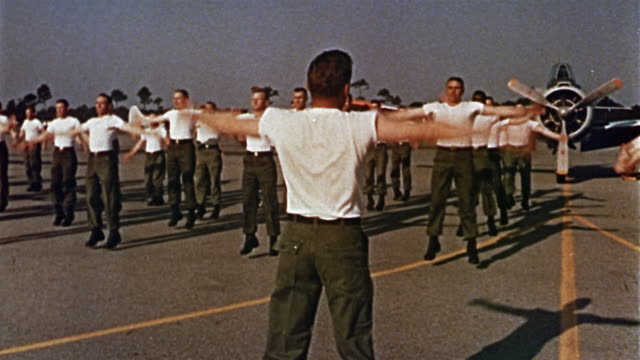 vidéos et rushes de 1960s medium shot us soldiers exercising (jumping jacks) in white t-shirts - armée américaine