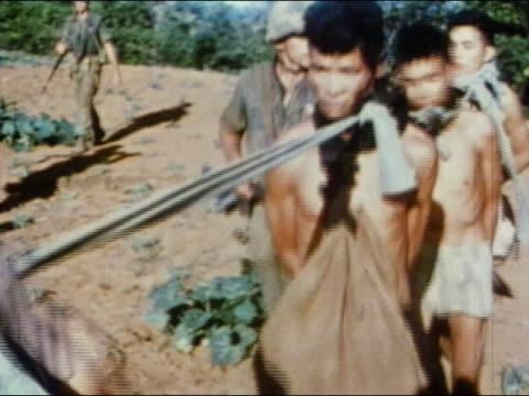 1960s medium shot viet cong pows stripped to underwear walking while tied together by their necks / vietnam - vietnamkrieg stock-videos und b-roll-filmmaterial