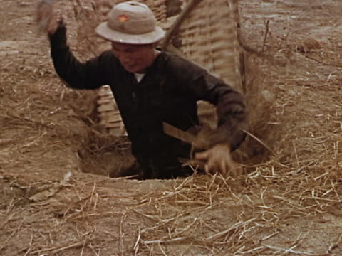 1960s / medium shot viet cong soldier climbing out of underground hiding hole / vietnam - ベトコン点の映像素材/bロール