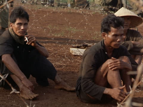 1960s medium shot Vietnamese men sitting on the ground near barbed wire / Vietnam