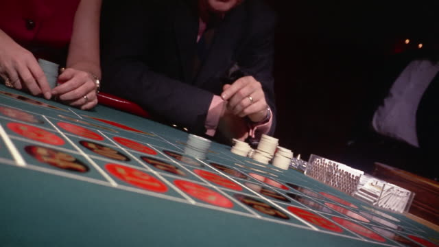 1960s medium shot woman and man sitting at roulette table / woman collecting winnings + making faces at man - roulette stock videos & royalty-free footage