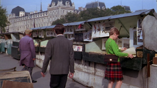1960s medium shot woman and men looking at art prints at street vendors stands / paris - book shop stock videos & royalty-free footage