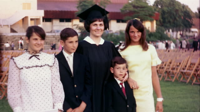 vídeos y material grabado en eventos de stock de 1960s medium shot woman in cap and gown standing with children + smiling at cam on commencement day - familia con cuatro hijos