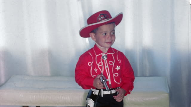 1960s medium shot young boy in cowboy costume shooting gun at CAM
