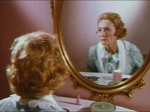 stockvideo's en b-roll-footage met 1960s medium shot zoom in middle-aged looking in mirror / examining face more closely in handheld mirror / audio - prelinger archief