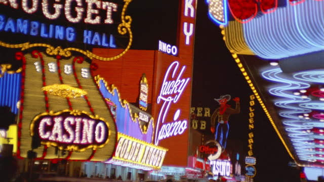 1960s medium shot zoom out neon signs outside las vegas casinos at night - medium shot stock videos & royalty-free footage