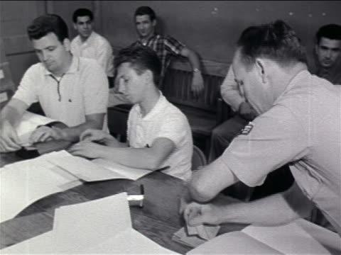 stockvideo's en b-roll-footage met 1960s men at tables enlisting in military / vietnam war / newsreel - in dienst gaan
