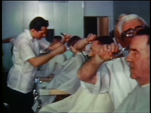 1960s men cutting hair in busy barbershop / industrial