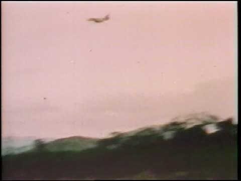 1960s military jet dropping napalm which explodes on ground / vietnam war / documentary - 空爆点の映像素材/bロール