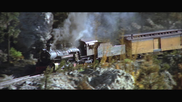 1960s cu ts miniature railroad train right speeding through rocky mountain country replica - 1960 1969 stock-videos und b-roll-filmmaterial